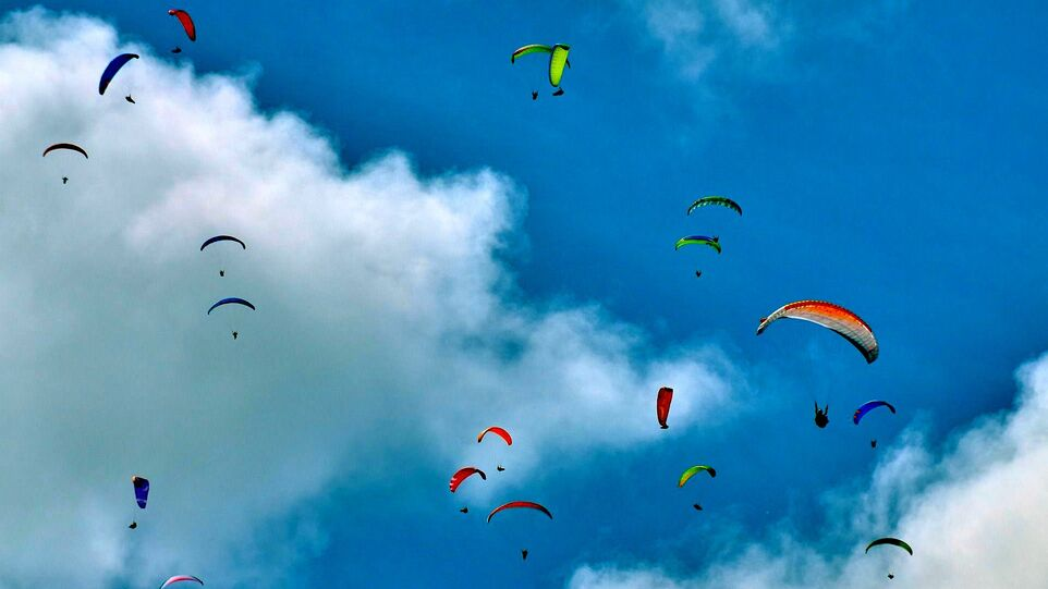 The picture shows several colourful paragliders in the sky.