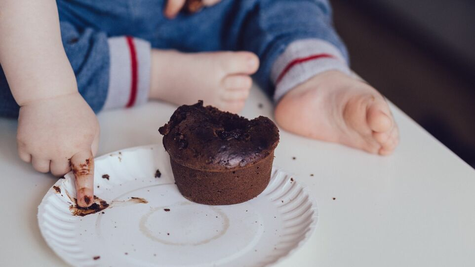 The picture shows a child with a muffin.